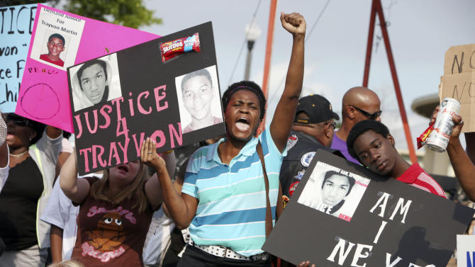 FILE- In this March 22, 2012 file photo, Lakesha Hall, 32, of Sanford, center, and her son, Calvin Simms, 12, right, gather early for a rally for Trayvon Martin, the black teenager who was fatally shot by George Zimmerman, a neighborhood watch captain, in Sanford, Fla.  The central Florida suburb of Sanford is getting back to normal a year after Zimmerman shot and killed Martin. (AP Photo/Julie Fletcher, File)