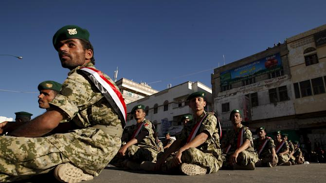 Army soldiers loyal to the Houthi group sit on the ground as they wait to march during a rally commemorating the anniversary of South Yemen's independence from British colonial rule, in Yemen's capital Sanaa