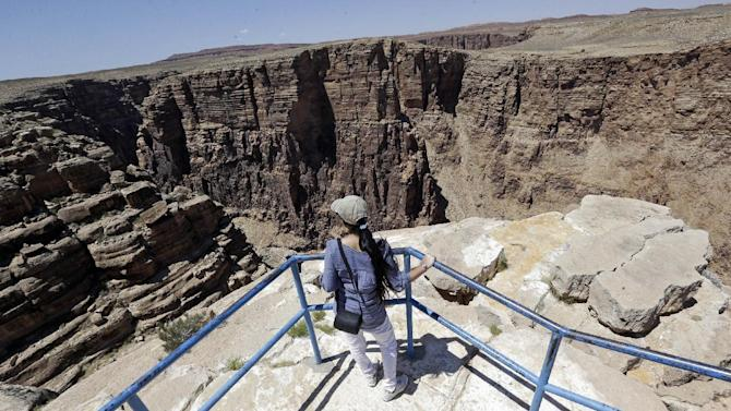 A unidentified tourist looks from a view point along the Little Colorado River Gorge Saturday, June 22, 2013, on the Navajo reservation near Cameron, Ariz., outside the boundaries of Grand Canyon National Park, near where Nik Wallenda, the Florida-based daredevil, will bid to walk on a tightrope stretched across the Little Colorado River Gorge. The event, which will be broadcast on live television at 8 p.m. EDT on Sunday with a 10 second delay. Wallenda will walk a third of a mile across a wire suspended 1,500 feet above the river. (In comparison, the Empire State Building in New York City is 1,454 feet high). (AP Photo/Rick Bowmer)