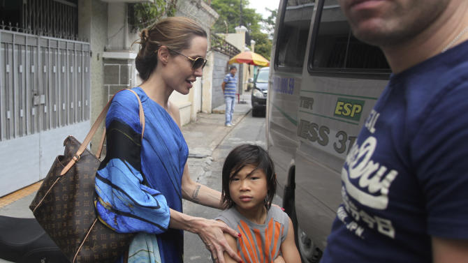 American actress Angelina Jolie, left, and her adopted son Pax Thien get on a minivan to leave a Vietnamese restaurant in Ho Chi Minh City, Vietnam, after lunch on Friday, Nov. 11, 2011. Hollywood power couple Jolie and Brad Pitt and their six children are on a visit to Vietnam, where Pax was born. (AP Photo/Na Son Nguyen)