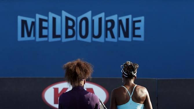 Serena, left, and Venus Williams of the United States walk on the court during their doubles match against  Camila Giorgi of Italy and Stefanie Voegele of Switzerland at the Australian Open tennis championship in Melbourne, Australia, Thursday, Jan. 17, 2013. (AP Photo/Aaron Favila)