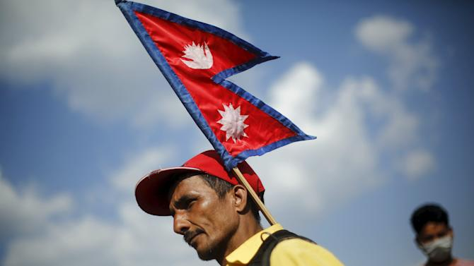 A displaced earthquake victim carries a Nepalese national flag as he waits in a line to receive food and water at an open ground, in Kathmandu
