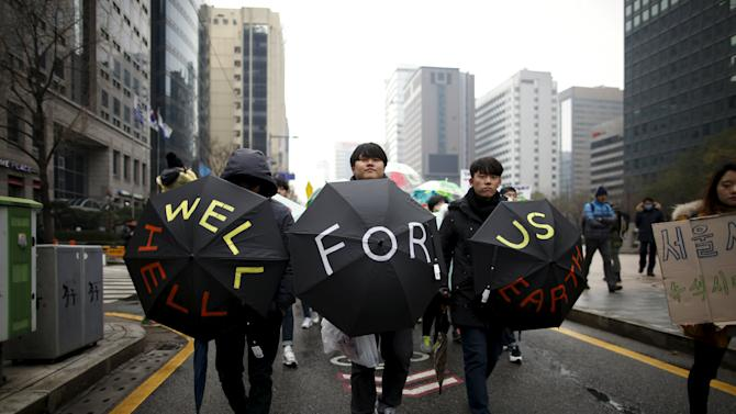 Participants holding umbrellas march during a rally ahead of the 2015 Paris Climate Change Conference, known as the COP21, in central Seoul