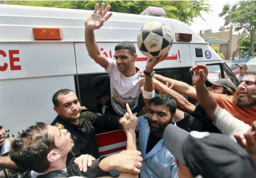 Palestinian soccer player Al-Sarsak waves to people upon his arrival in Gaza City