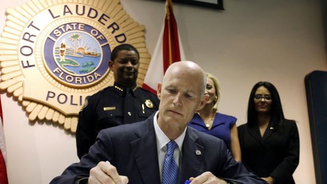 "Gov. Rick Scott signs a new law aimed at controlling the state's ""pill mills"" by penalizing doctors who over prescribe painkillers, tightening rules for operating pharmacies and authorizing a prescription-drug monitoring database during a ceremony at a Fort Lauderdale, Fla. police station, Friday, June 3, 2011. Florida is considered the epicenter of prescription drug abuse, with pain-management clinics supplying drug dealers and addicts with illicit prescription painkillers. Many of those people come from out of state. (AP Photo/J Pat Carter)"