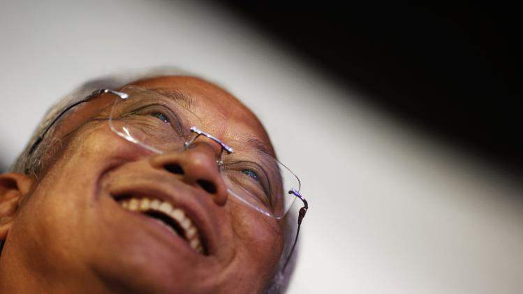 Anti-government protest leader Suthep smiles before addressing his supporters from the stage near the Government House in Bangkok