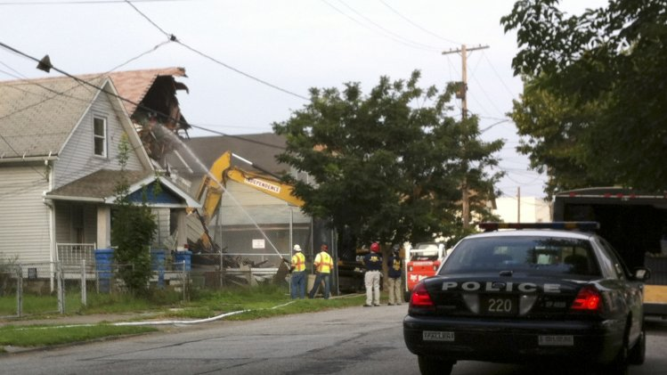 A wrecking crew uses a hydraulic excavator to begin the demolition of the rundown house where three young women were imprisoned and tortured by Ariel Castro in Cleveland