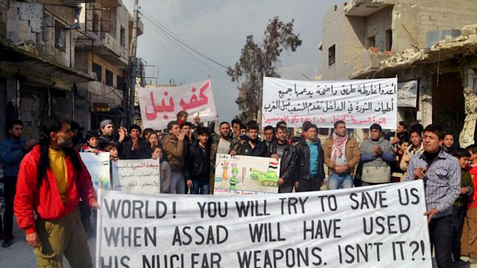 """This citizen journalism image provided by Edlib News Network, ENN, which has been authenticated based on its contents and other AP reporting, shows anti-Syrian regime protesters carry banners during a demonstration, at Kafr Nabil town, in Idlib province, northern Syria, Friday, Feb. 15, 2013. Heavy fighting for control of the international airport in the northern Syrian city of Aleppo and a major military air base nearby has killed some 150 rebels and government soldiers over the past two days, activists said Friday. The Arabic banner, background right, reads: """"prepare a clear roadmap backed by all those in the revolution inside the country that be put forward for the people before the West."""" (AP Photo/Edlib News Network ENN)"""