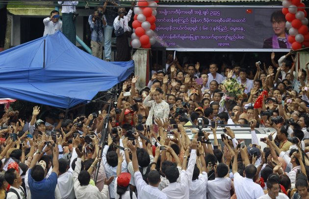 Myanmar pro-democracy leader Suu Kyi waves to supporters as she leaves National League for Democracy party headquarters after attending her 68th birthday ceremony in Yangon