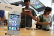 File photo shows the Apple iPhone 4Gs displayed at an Apple store in 2011. Apple becomes the focus of the technology universe Wednesday as the world awaits a new iPhone with a big, beautiful touchscreen and connectivity to blazingly fast telecom networks