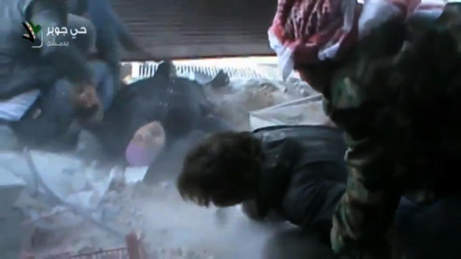 This image taken from video obtained from Shaam News Network, which has been authenticated based on its contents and other AP reporting, shows an injured Syrian woman rescued by rebels from a firefight in a street in the Jobar neighborhood in Damascus, Syria, Wednesday, April 10, 2013. Syrian President Bashar Assad's troops battled rebels in the outskirts of Damascus on Wednesday and pressed on with a counteroffensive against opposition fighters in the south to prevent their advance on the capital.(AP Photo/Shaam News Network via AP video)