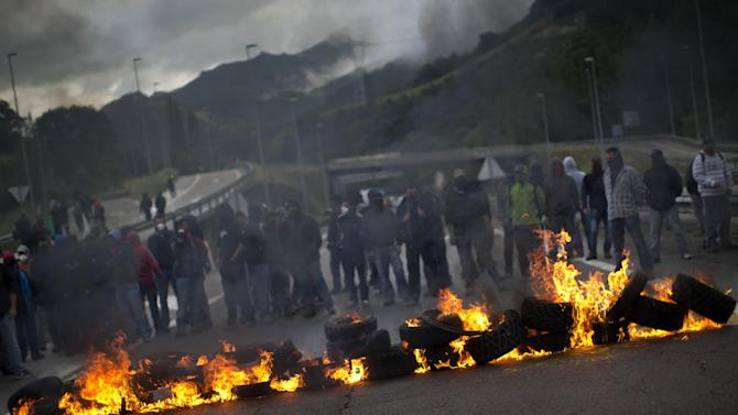 Miners block a motorway making a barricade with burning tires in Campomanes, Oviedo, Spain, Tuesday, June 12, 2012. Strikes, road blockades, and mine sit-ins continue as 8,000 mineworkers at over 40 coal mines in northern Spain continue their protests against government action to cut coal subsidies. (AP Photo/Emilio Morenatti)