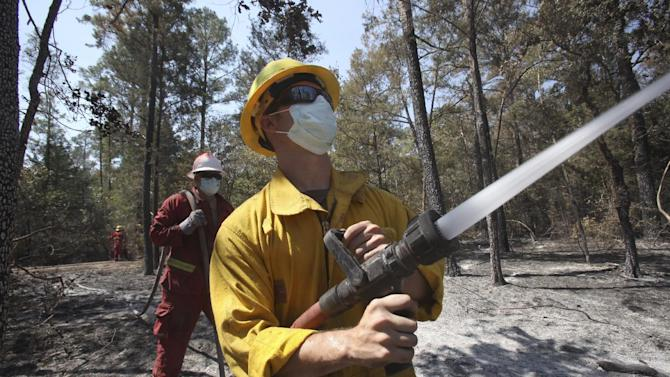 Volunteer fireman Ryan Mills douses hot spots with water on a wildfire near Bastrop, Texas, Friday, Sept. 9, 2011. Texas is suffering its worst wildfire outbreak in state history. The Bastrop-area fire has been the largest of nearly 190 wildfires the forest service says erupted this week, leaving nearly 1,700 homes statewide in charred ruins, killing four people and forcing thousands of people to evacuate.   (AP Photo/LM Otero)