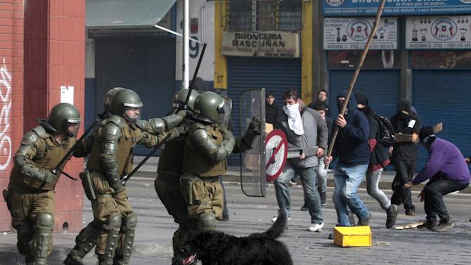 FILE - In this July 14, 2011 file photo, a dog runs as police clash with student protesters in Santiago, Chile. Stray dogs are truly Man's Best Friend for thousands of students and workers who demonstrate and clash with police nearly every day to press demands for education improvements, redistribution of Chile's wealth and environmental protections.  (AP Photo/Luis Hidalgo, File)
