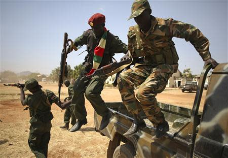 SPLA soldiers jump from a vehicle in Juba