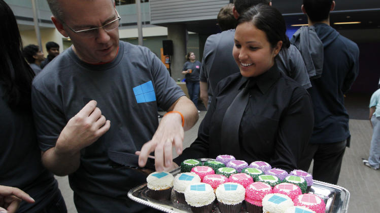 A Microsoft employee reaches for cupcakes being served with the company's logo atop during an event unveiling a new Microsoft Windows operating system Thursday, Oct. 25, 2012, at the company's headquarters in Redmond, Wash. Windows 8, attempts to bridge the gap between personal computers and fast-growing tablets with its touch-enabled interface. It is the most dramatic overhaul of the personal computer market's dominant operating system in 17 years. (AP Photo/Elaine Thompson)