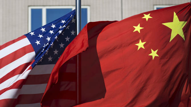 U.S. flag and China's flag flutter in winds at a hotel in Beijing Wednesday, Sept. 5, 2012. U.S. Secretary of State Hillary Rodham Clinton is in Beijing to press Chinese authorities to agree to peacefully resolve disputes with their smaller neighbors over competing territorial claims in the South China Sea. But as she began her meetings here, China questioned the stated neutrality of the United States. (AP Photo/Andy Wong)