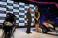 "Yamaha Motors brand ambassador and Bollywood actress Deepika Padukone (R), with Yamaha Motors President and CEO Hiroyuki Yanagi, poses with new ""Ray"" scooters during a product launch in Hyderabad"