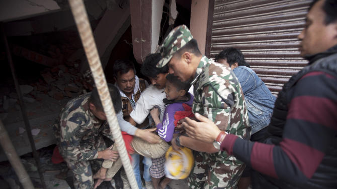Volunteers carry an injured boy after rescuing him from the debris of a building that was damaged in an earthquake in Kathmandu, Nepal, Saturday, April 25, 2015. A strong magnitude-7.9 earthquake shook Nepal's capital and the densely populated Kathmandu Valley before noon Saturday, causing extensive damage with toppled walls and collapsed buildings, officials said. (AP Photo/ Niranjan Shrestha)