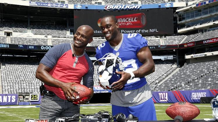 New York Giants' Jon Beason, right, demonstrates the communication devices that are powered by Duracell Quantum batteries to actor Taye Diggs at MetLife stadium on Wed., Aug. 27, 2014 in E.Rutherford, N.J. More than 650 of these batteries power every NFL game. (Photo by Mark VonHolden/Invision for Duracell/AP Images)