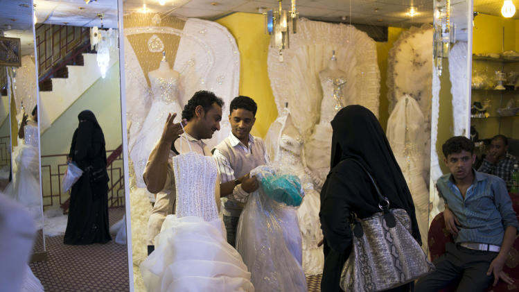 Yemeni women shop for wedding dresses in Sanaa, Yemen, Wednesday, Dec. 26, 2012. While most Yemeni women don the traditional niqab, gender separated weddings bring out the latest in western-style wedding dresses. (AP Photo/Alex Potter)