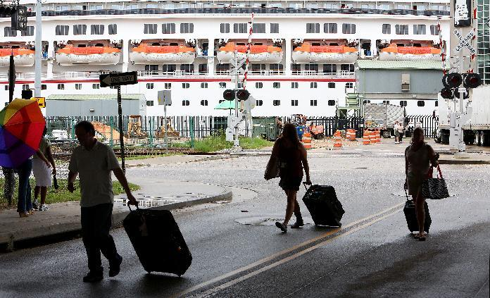 Passengers disembark from the Carnival Conquest after the cruise ship arrived at the Alabama Cruise Terminal on the Mobile River on Sunday, July 7, 2013, in downtown Mobile, Ala. The Conquest was diverted from New Orleans to Mobile after a tugboat sank in the Mississippi River Saturday, closing the river. (AP Photo/AL.com, Mike Brantley)