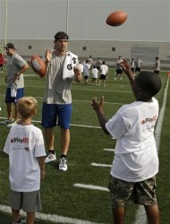 Indianapolis Colts rookie quarterback Andrew Luck plays catch with kids at an NFL football Play 60 youth clinic at the Cleveland Browns training facility in Berea, Ohio Friday, June 29, 2012. (AP Photo/Mark Duncan)