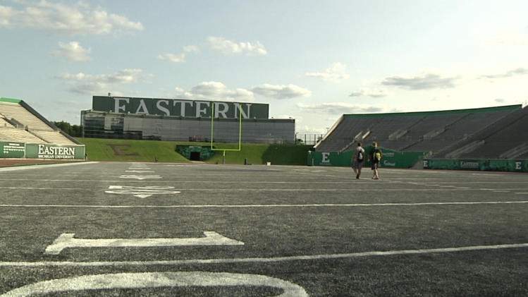 In this photo taken on Aug. 15, 2014, a pair Eastern Michigan players walks across he field after NCAA college football practice at Rynearson Stadium in Ypsilanti, Mich.. The school has replaced the stadium's green artificial turf with gray FieldTurf