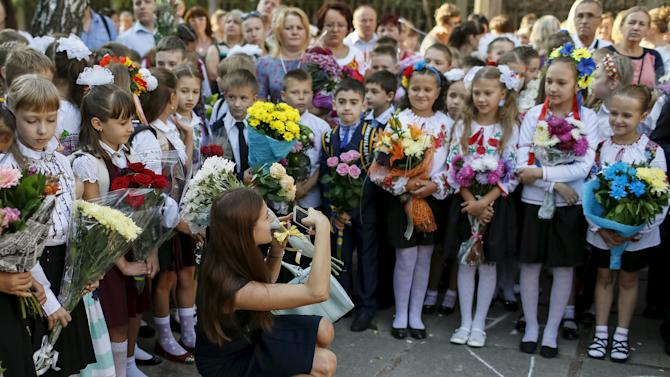 Woman takes pictures as first graders attend a ceremony to mark the start of another school year in Kiev