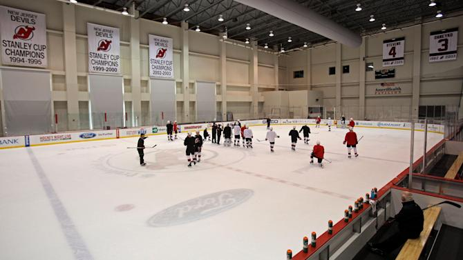New Jersey Devils president and general manager Lou Lamoriello, bottom right, looks on during a morning skate on Saturday, Dec. 27, 2014, in Newark, N.J. Devils are replacing the fired Pete DeBoer with a three-headed coaching staff. Former Washington Capitals coach Adam Oates, ex-Devils assistant and star defenseman Scott Stevens and Lamoriello will split duties on the bench. (AP Photo/Adam Hunger)