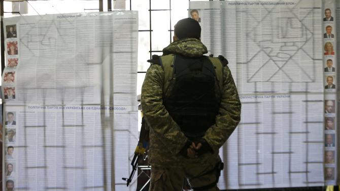 A Ukrainian government forces member, who takes part in a military operation eastern regions of Ukraine, stands in front of candidate information sheets as he visits a polling station during a parliamentary election in the town of Kramatorsk