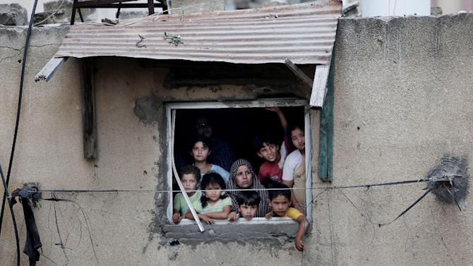 FILE - In this Monday, July 21, 2014, file photo, a Palestinian family watches rescuers searching for bodies and survivors under the rubble of homes which were destroyed by an Israeli missile strike, in Gaza City. Disagreement over whether to lift the Gaza blockade is a key stumbling block to ending more than two weeks of fighting between the Islamic militant Hamas and Israel. Some in Gaza say they would rather endure more fighting than return to life under the blockade. (AP Photo/Khalil Hamra, File)