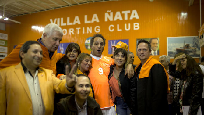 In this Aug. 29, 2015 photo, Daniel Scioli, the provincial governor of Buenos Aires who's running for president, poses for a picture with supporters during the half-time break of an indoor soccer game that he was playing in the outskirts of Buenos Aires, Argentina. Scioli is no stranger to the bright lights of politics. He was vice president in the administration of Cristina Fernandez's predecessor and late husband, Nestor Kirchner, and currently oversees the country's largest province, which includes about a third of Argentine voters. (AP Photo/Natacha Pisarenko)