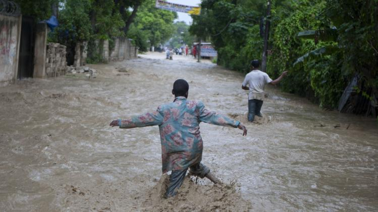 Residents wade through a flooded street caused by heavy rains from Hurricane Sandy in Port-au-Prince, Haiti, Thursday, Oct. 25, 2012. Hurricane Sandy rumbled across mountainous eastern Cuba and headed toward the Bahamas on Thursday as a Category 2 storm, bringing heavy rains and blistering winds.  (AP Photo/Dieu Nalio Chery)