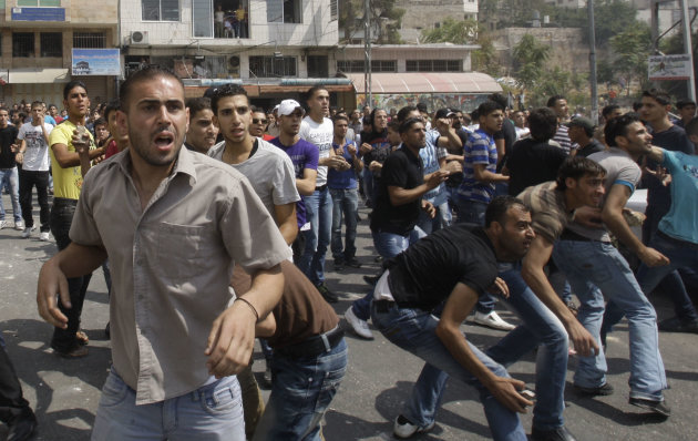 Palestinian demonstrators throw stones towards Palestinian police during a protest near the municipality building in the West Bank city of Hebron, Monday, Sept. 10, 2012. Palestinian demonstrators fed