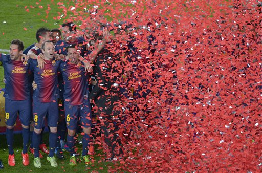FC Barcelona's players, Jordi Alba, left, Andres Iniesta, second from left, and Xavi Hernandez, right, celebrate winning the Spanish League after the La Liga soccer match between FC Barcelona and Vall