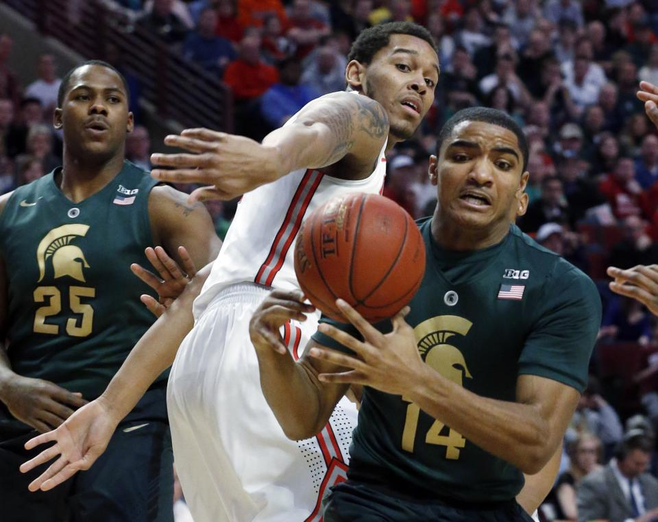 Ohio State's Amir Williams knocks the ball out of the hands of Michigan State's Gary Harris (14) during the first half of an NCAA college basketball game at the Big Ten tournament Saturday, March 16, 2013, in Chicago. (AP Photo/Charles Rex Arbogast)