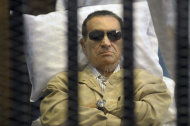 FILE - In this Saturday, June 2, 2012 file photo, Egypt's ex-President Hosni Mubarak lays on a gurney inside a barred cage in the police academy courthouse in Cairo, Egypt. An Egyptian prison official says Hosni Mubarak's health has taken a turn to the worst and is likely to be moved out of his prison hospital to a military facility nearby. The official said Tuesday doctors reported that the 84-year old former president has fallen unconscious. He said they have used a defibrillator to restart his heart, and have been administering breathing aid. (AP Photo, File)