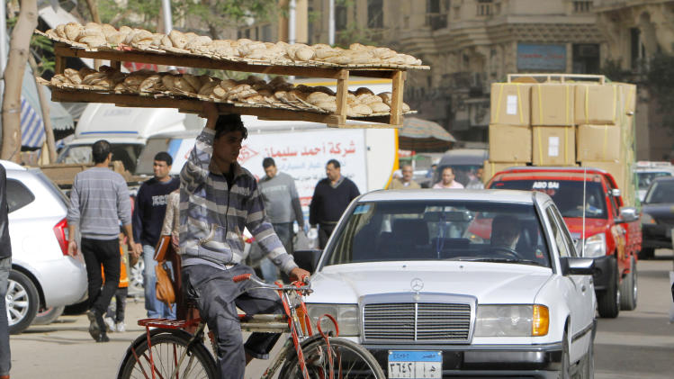 An Egyptian bread vendor rides his bicycle in downtown Cairo, Egypt, Saturday, March 16, 2013. Owners of state-subsidized bakeries protested Saturday against changes to the distribution system of subsidized wheat. It comes amid economic reforms the government is seeking to implement to boost the economy and ensure subsidized bread reaches millions of poor Egyptians who complain that the bakeries sell the wheat for a profit. (AP Photo/Amr Nabil)