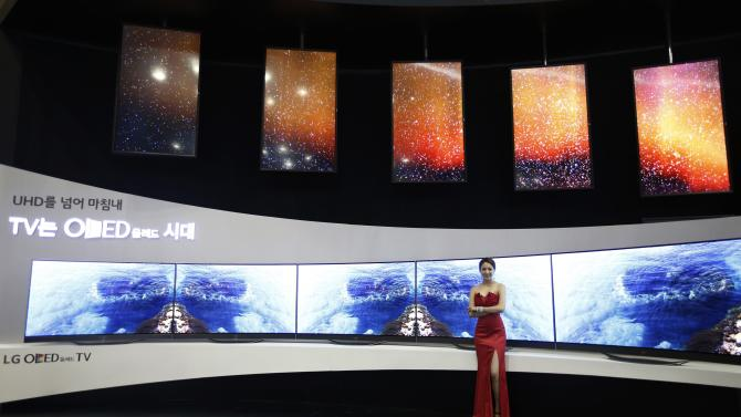 A model poses in front of LG Electronics' flexible OLED TV sets during the 2014 Korea Electronics Show in Goyang