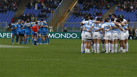 Italy's and Argentina's players stand for a minute of silence for the victims of extreme rainfall that flooded eastern parts of the Mediterranean island of Sardinia, during their rugby test match at t