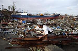A typhoon survivor retrieves nails from planks to build a makeshift shelter in Typhoon Haiyan battered Tacloban