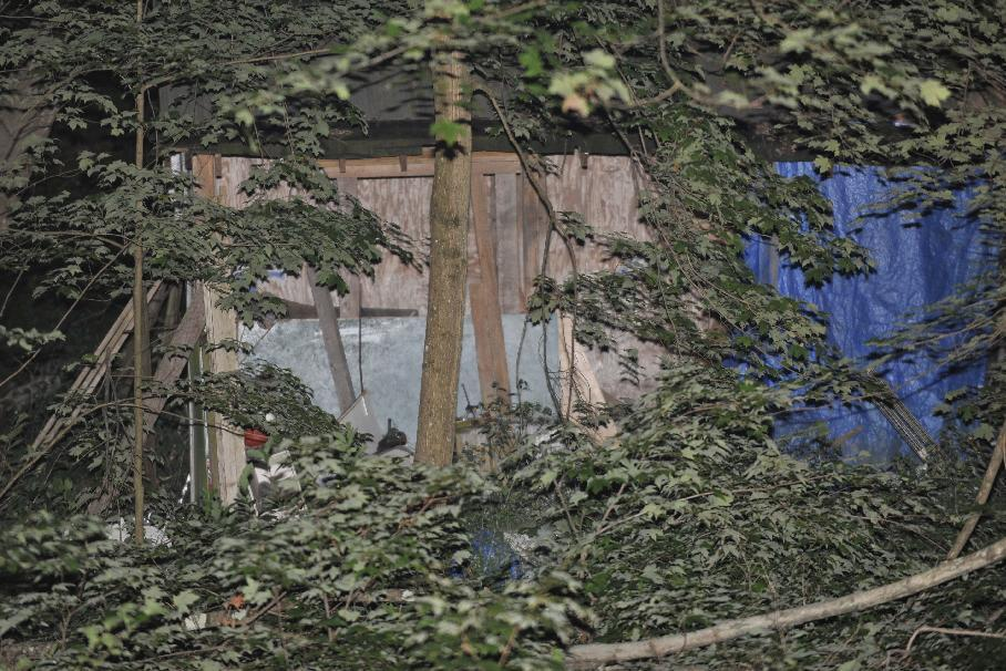 A Pennsylvania State Police Trooper guards the dilapidated home of alleged shooter 59-year-old Rockne Newell, Tuesday, Aug. 6, 2013 in Saylorsburg, Pa. Police said Newell entered the Ross Township Municipal Building Monday evening and shot several people. (AP Photo/Chris Post)