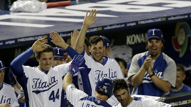 Italy's Tyler LaTorre (32) celebrates as he comes to the dugout after scoring on a double by Anthony Granato during the second inning of a World Baseball Classic game against the United States Saturday, March 9, 2013, in Phoenix. (AP Photo/Charlie Riedel)
