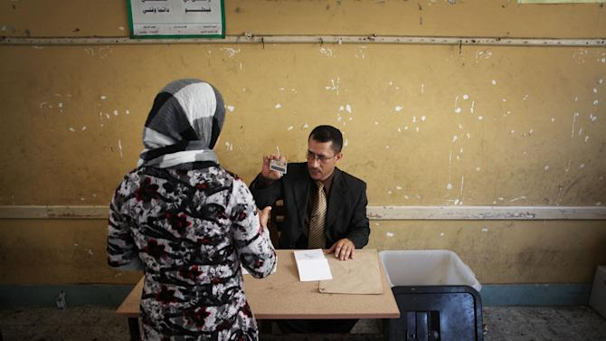 An Egyptian woman shows her ID to the polling station chief during the second day of the presidential runoff election in Alexandria, Egypt, Sunday, June 17, 2012. Egyptians are choosing between a conservative Islamist and Hosni Mubarak's ex-prime minister in a second day of a presidential runoff that has been overshadowed by the domination of the country's military. (AP Photo/Manu Brabo)