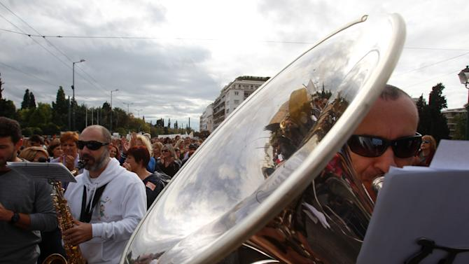 Members of Athens municipal brass band play their instruments during a demonstration by municipal employees on Tuesday, Nov. 20, 2012. About 2,000 people took part in the protest, against government plans to place 2,000 civil servants on notice ahead of reassignment or potential dismissal. Greece faces a tense wait Tuesday for vital bailout money as finance ministers from the 17 European Union countries that use the euro try to reach an agreement on how to put the country's economic recovery back on the right track. (AP Photo/Thanassis Stavrakis)