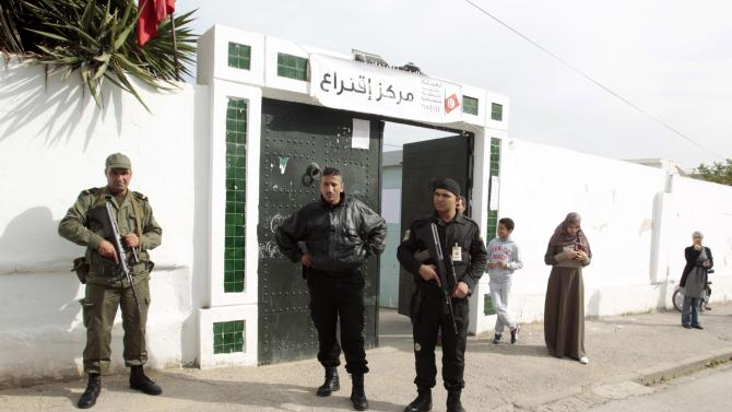 People stand outside a polling station in Tunis