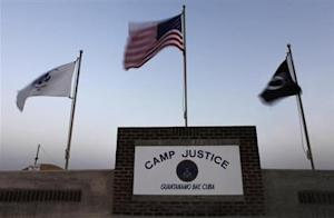 Flags wave above the sign posted at the entrance to Camp Justice at Guantanamo Bay U.S. Naval Base