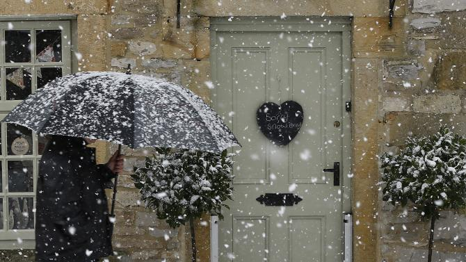 A man walks past a shop closed because of snow in Ashford In The Water