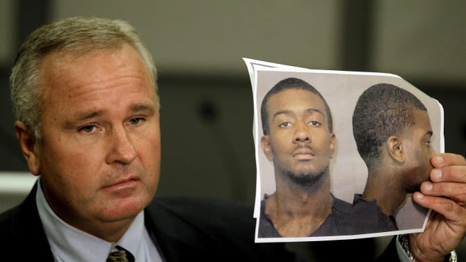 Auburn Police Chief Tommy Dawson holds up a photo of Desmonte Leonard, 22,  of Montgomery, Ala., the suspect wanted for fatally shooting three people, including two former Auburn University football players, and wounding another three people during a party at an apartment complex near the school, at a news conference Sunday, June 10, 2012, in Auburn, Ala. (AP Photo/David Goldman)